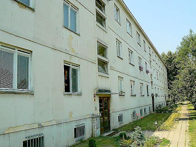 V levé části fotografie je vidět pod fasádou struktura úzkých betonových bloků [1]